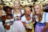 Young women in dirndl dresses pose with beer mugs at the Oktoberfest beer festival.