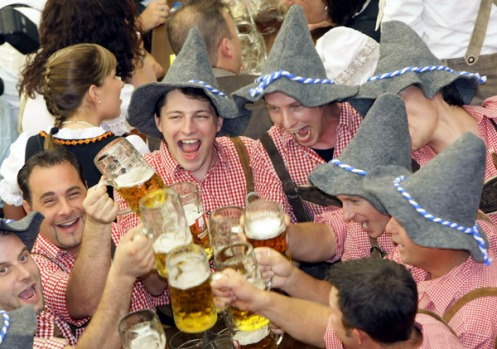 People in traditional Bavarian clothes toast with beer during the opening ceremony for the 176th Oktoberfest.