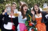 Young women wave with their beer steins while riding a decorated coach to the opening.