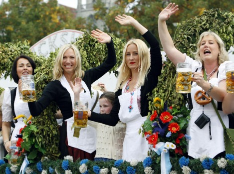 Waitresses wave with their beer steins while riding a decorated coach to the opening of Oktoberfest.