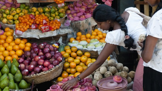 A woman selects fruit from a stall in Galle.