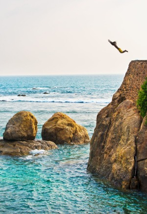 A man hurls himself from a cliff near Galle.