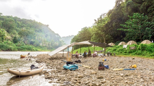 Camp is made up of tents set up by a bend of the Upper Navua.