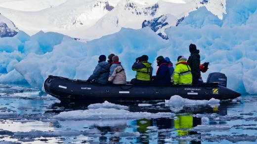 Tourists explore rugged blue icebergs cruising in an inflatable boat.