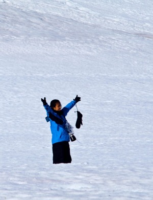 A tourist on a snowy mountainside celebrates being in Antarctica.
