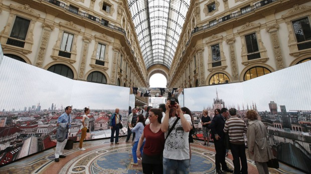 A tourist takes photos of an installation on Milan's history at the restored Galleria Vittorio Emanuele II in Milan, ...