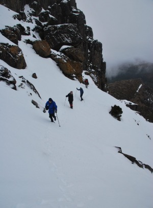 Walkers go Indian file along the side of Cradle Mountain.