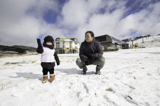 Sherwin Sinlao and son, Shiloh, of Brighton, enjoy the snow at Perisher on Wednesday.