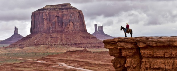 A Navajo man on a horse poses for tourists in front of the Merrick Butte in Monument Valley Navajo Tribal Park, Utah.