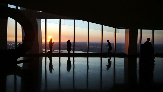 People view the sunrise at the newly built One World Observatory at One World Trade Center on the day it opened to the ...
