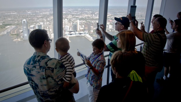 Visitors to One World Observatory make pictures and view parts of New Jersey after a ribbon-cutting ceremony, Friday, ...
