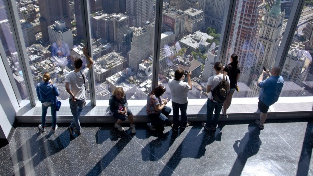 Some of the first visitors to the One World Observatory view the city and beyond from the 101st floor after a ...