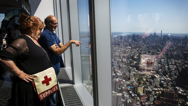Visitors to the newly opened One World Observatory take photographs and look out on Manhattan and the outer boroughs of ...