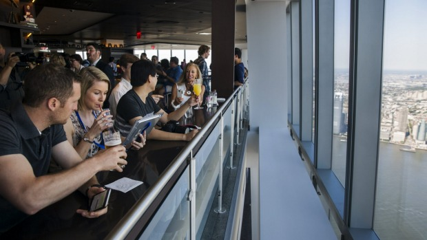 Visitors sit down for drinks and food in a restaurant as they look out the windows of the newly opened One World Trade ...