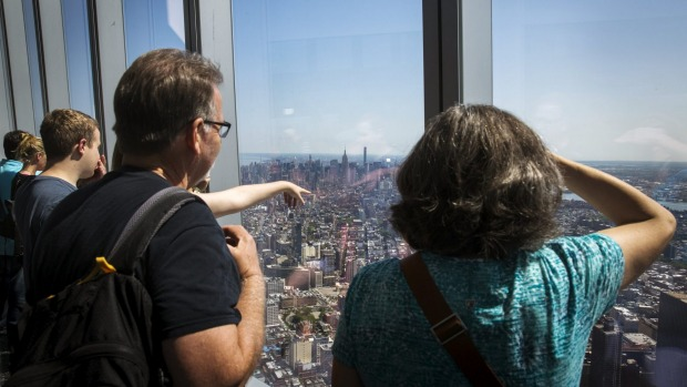 Visitors to the newly opened One World Trade Observatory take photographs and look out on Manhattan and the outer ...