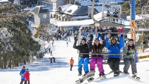 A bevy of keen learner boarders head to the top of Bourke Street on Mt Buller for their lesson.