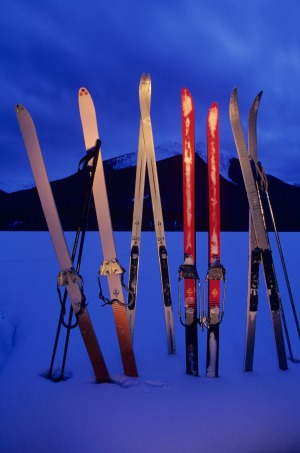 Backcountry skiers' skis stand propped snowbank,