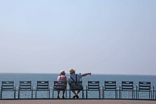Two elderly people sit on the blue chairs of the Promenade Des Anglais near the Mediterranean Sea during a warm and ...