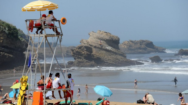 Lifeguards sit in an coastguard watchtower as people enjoy the sunny weather on a beach in Biarritz, southwestern France.