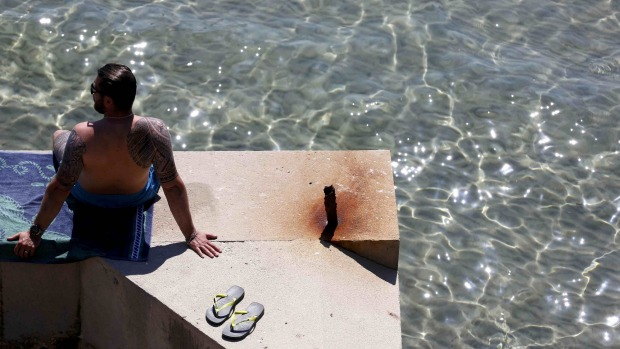 A man takes in the sun along the Mediterranean Sea during a warm and sunny day in Marseille, France.