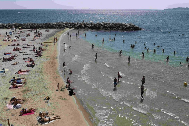 People swim in the Mediterranean Sea during an unusually warm and sunny day in Marseille, France.