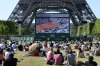 People sit on the grass of the Champ de Mars to watch the women's semi-final match of the Roland Garros 2015 French ...