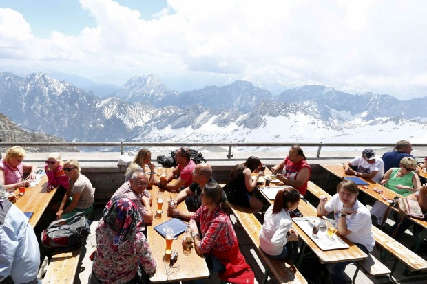 Tourists enjoy sunny weather in Germany's highest beer garden atop of the 2,962 metre Zugspitze mountain in Grainau near ...
