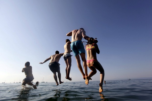 People jump into the sea on a hot summer day in Fiesa, Slovenia.