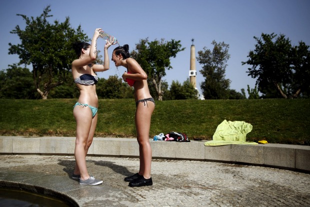 Jennifer Perez, 19, pours water on her friend Marijose Sanchez, 19, as they try to cool off while sunbathing during a ...