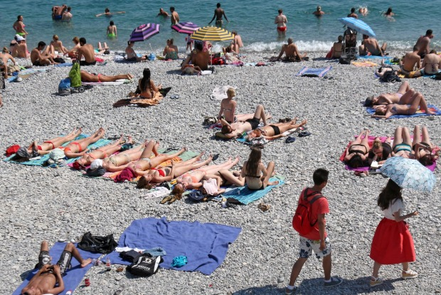 People sunbathe on the beach in Nice, southeastern France, Friday. Temperatures in the area rose to 28 degrees Celsius.