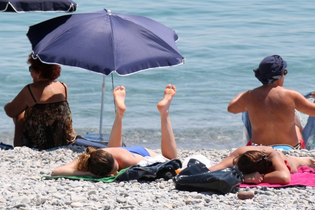 People sunbathe on the beach in Nice, southeastern France. Temperatures in the area rose to 26 degrees Celsius.