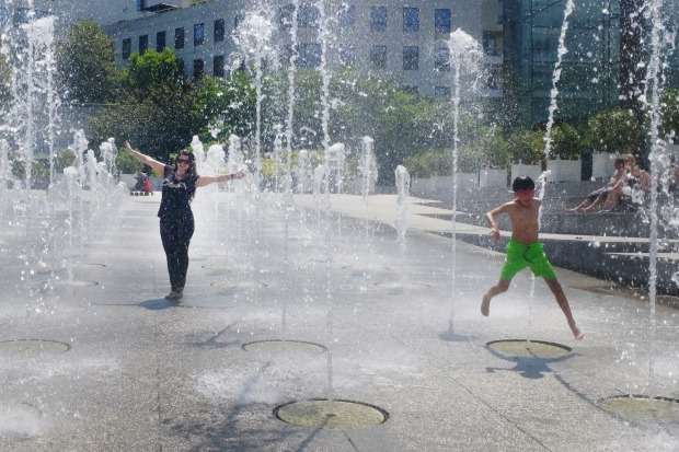 People cool down in the  fountains at Andre Citroen square in Paris, France.