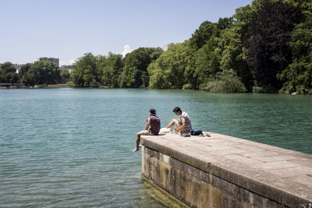 People have lunch in front of the lake of the Parc de la Tete d'or, in Lyon, central France.