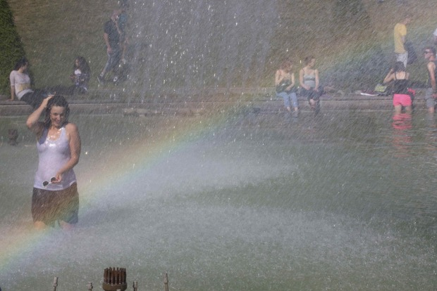 A rainbow appears in the spray as a young woman cools off from the heat in the fountains across from the Eiffel Tower as ...