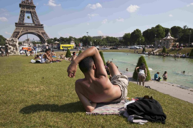 People take in the sun as others cool off from the heat in the fountains across from the Eiffel Tower as unusually warm ...