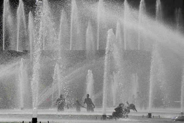 People cool off from the heat in the fountains across from the Eiffel Tower as unusually warm temperatures arrive in ...