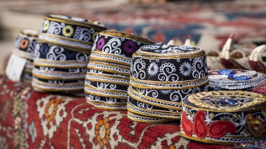 Taqiyah, traditional muslim hats placed on a typical carpet sold on a local market in Icheri Sheher (Old Town) in the ...