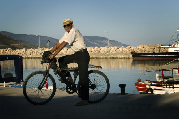 A local man shows off his self-modified bicycle, now with a toolset attached to the steering shaft, in the small coastal ...