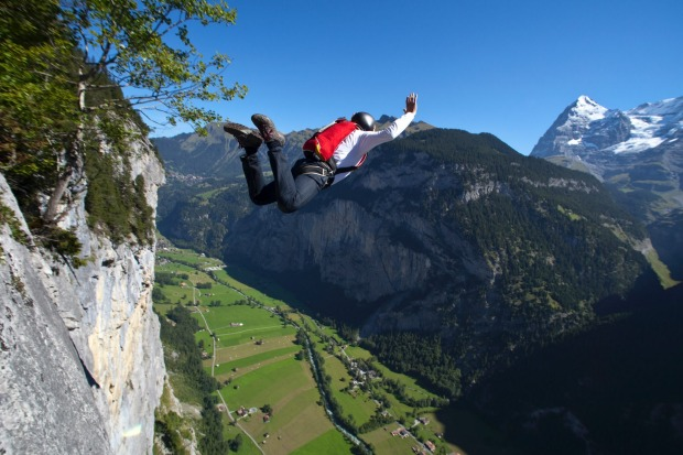 A BASE jumper launches into Lauternbrunnen valley.