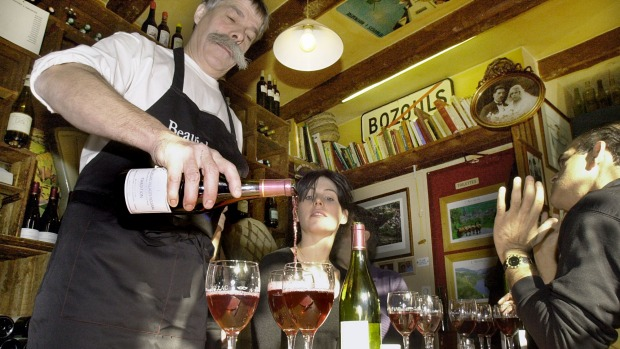 A cafe owner pours wine for his customers in the very different drinking culture of Paris.
