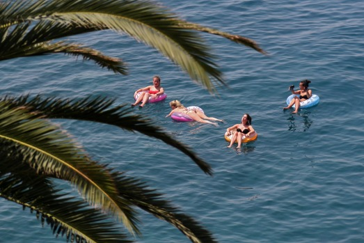 Girls have a swim in the Mediterranean sea, in Nice, southeastern France.