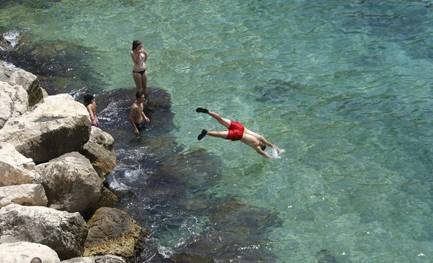 People dive into the Mediterranean sea in Marseille, southern France.