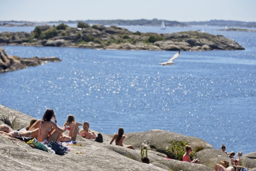People sunbathe on the cliffs of Saltholmen, on the outskirts of Gothenburg, Sweden.