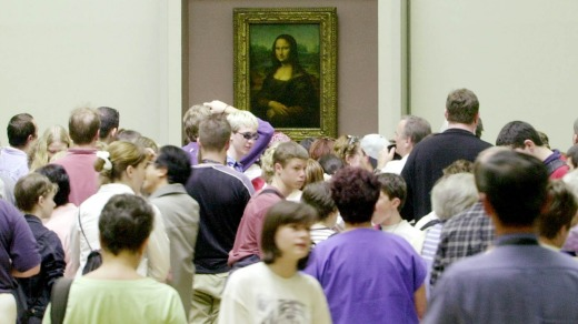 Visitors are packed around the Mona Lisa as they visit the Louvre.