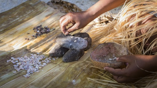 A woman makes shell money, whittling down shells into small shapes.