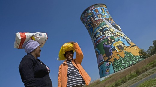 Two women chat in front of Orlando Power Station tower in Soweto, Johannesburg.