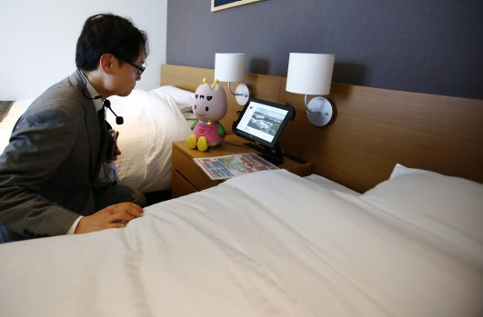 A man talks to concierge robot Tuly at the new robot hotel, aptly called Henn na Hotel or Weird Hotel, in Sasebo, ...