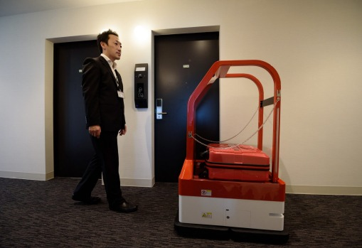 A guest follows a porter robot inside the Henn na Hotel.