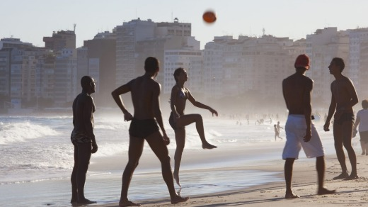 People of all ages play a hybrid of football and volleyball on Copacabana Beach.