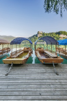 Boats parked on a wooden dock on Lake Bled, Slovenia.